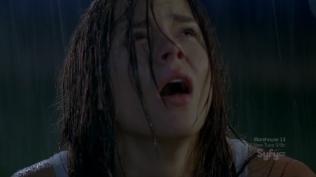 Close-up of traumatized actress gazing up at the rain at night.
