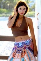 Medium close-up shot of actress Kacey Barnfield wearing a colorful skirt and brown crop top that shows of her belly button.