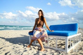 Actress Kacey Barnfield sitting on a beach wearing a colorful skirt and brown crop top.