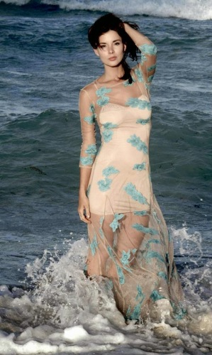 Actress Kacey Barnfield standing in a sea wearing a tight dress.