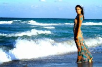 Actress Kacey Barnfield walking along a beach wearing a tight dress.