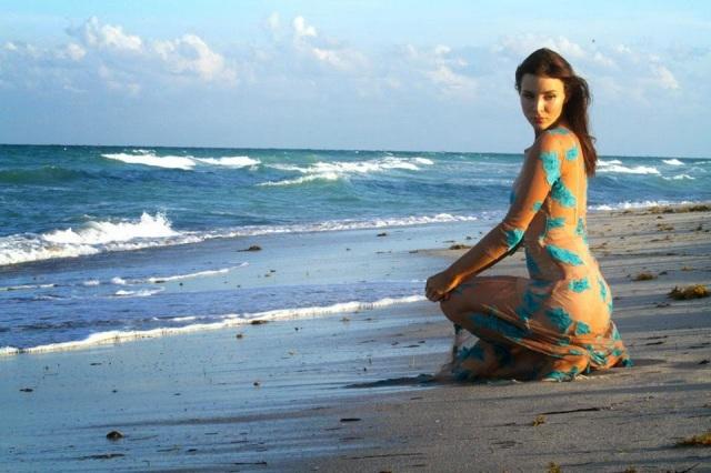 Actress Kacey Barnfield kneeling on a beach wearing a tight dress.