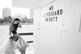 Black and white photo of actress Kacey Barnfield wearing a crop top and skirt near a No Lifeguard on Duty sign.