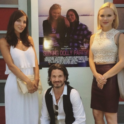 Kacey Barnfield, Michael Worth and Anya Monzikova standing in front of a poster for their movie.