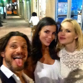 Michael Worth sticking his tongue out while next to two sexy actresses.