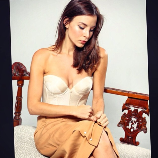 Kacey Barnfield sitting on a sofa wearing a corset top and light brown skirt