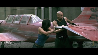 Actress pushing jet plane with Boris Kodjoe