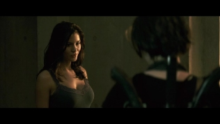 Actress talking to Milla Jovovich while wearing a dark vest.