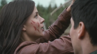 Actress with blood on her face unties her friend.