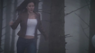 Actress wearing tight white shirt running through woods.