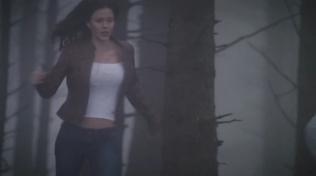 Actress wearing tight white shirt running through woods.