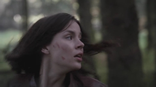 Actress with blood smeared on her face looking back as she runs scared.