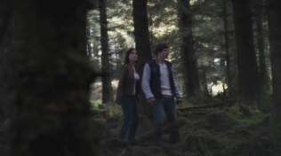Actress stood in a wood with friend.