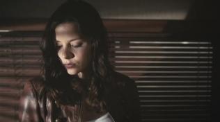 Kacey Clarke looking moody in front of Venetian blinds.