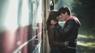 Actress embracing Oliver James outside a caravan motor home.