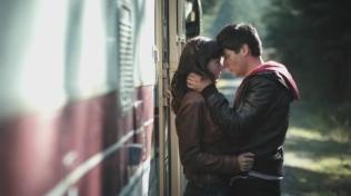 Actress embracing Oliver James outside a caravan motor home.