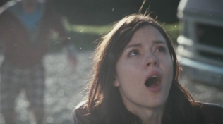 Actress looking up with her mouth open in disbelief.