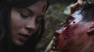Actress crying next to her dead friend's bloody face.