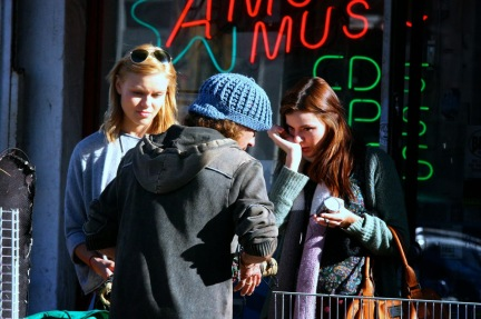 Kacey Barnfield and Anya Monzikova on set in front of a store.
