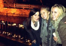 Three girlfriends in coats.