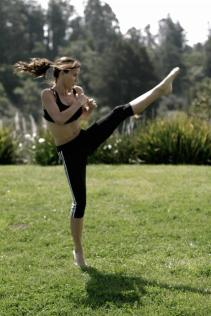 Kacey Barnfield doing high kick in a field.
