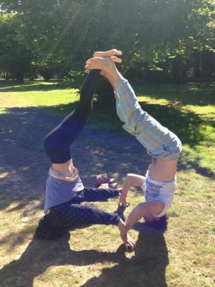 Two girls doing hand stands in a field.