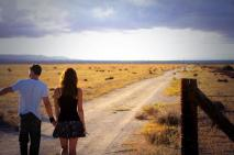Kacey Barnfield and Michael Worth walking down a long quiet road.