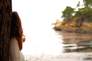 Kacey Barnfield looking out at the sea in Enchanting the Mortals movie.