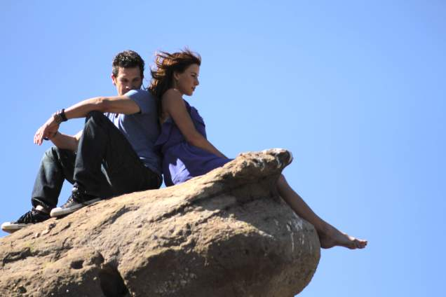 Michael Worth and Kacey Barnfield sitting on a cliff for Enchanting the Mortals movie.