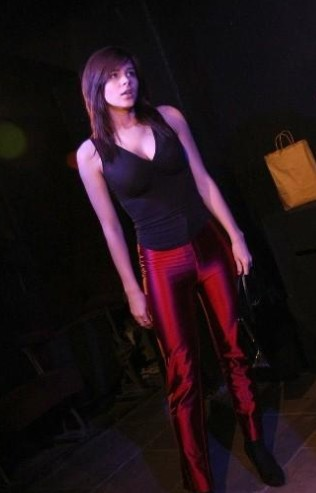 Kacey Barnfield performing in a tight black shirt and red pants.