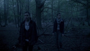 Kacey Barnfield walking through the darkened woods