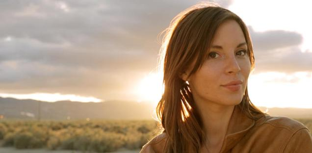 Kacey Barnfield standing in front of a sunrise