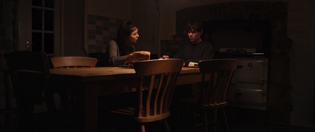 Kacey Barnfield and Christopher Rithin sitting at a dimly lit table