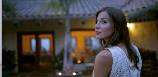 Kacey Barnfield looking over her shoulder at night