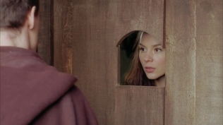 Kacey Barnfield looking through a hole in a door