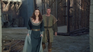 Kacey Barnfield walking through gates of a medieval village