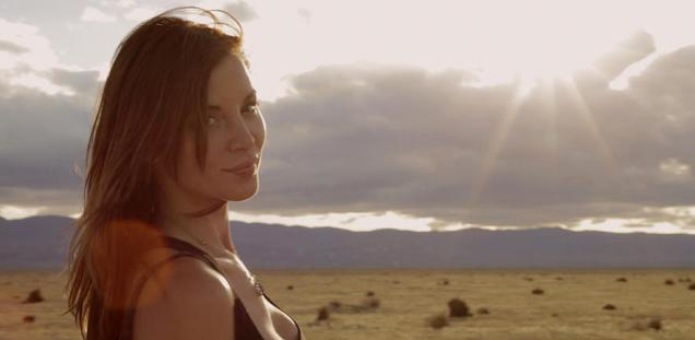 Kacey Barnfield looking at the camera with a cloudy sky behind her
