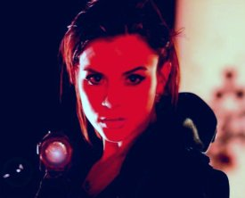 Kacey Barnfield staring into the camera with red lighting on her face
