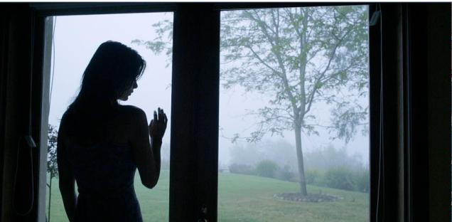 Silhouette of Kacey Barnfield in front of a large window