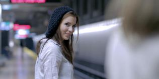 Kacey Barnfield wearing a beret and waiting at a train station