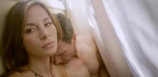 Kacey Barnfield and Michael Worth between the sheets of a bed