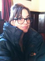 Kacey Barnfield wearing a big blue coat and glasses behind the scenes of Green Street 3 movie