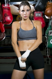 Kacey Barnfield standing next to boxing gloves wearing a sports bra