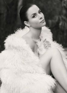 Kacey Barnfield wrapped in a furry blanket with head tilted up