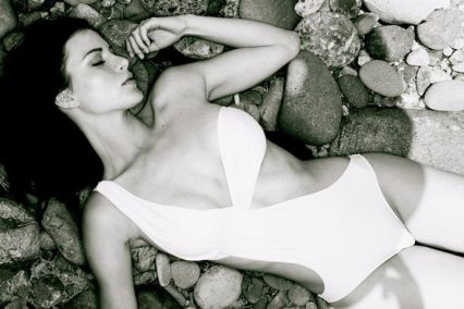 Kacey Barnfield lying on her back in a white swim suit