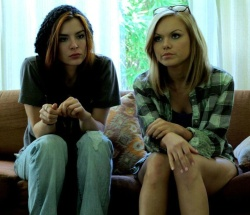 Kacey Barnfield and Anya Monzikova sitting on a couch looking thoughtful