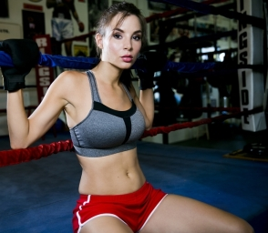 Kacey Barnfield sat in a boxing ring wearing red shorts and a sports bra