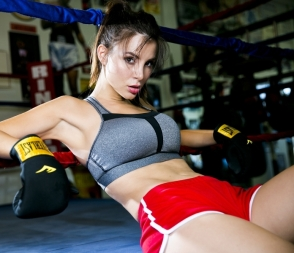 Kacey Barnfield lying back in a boxing ring wearing red shorts and a gray sports bra