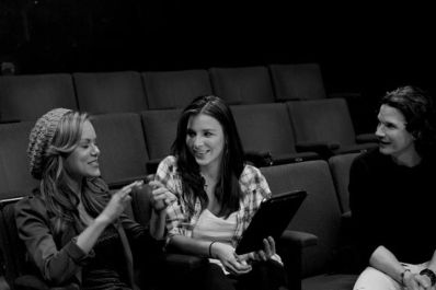 Anya Monzikova, Kacey Barnfield, and Michael Worth sitting in an empty theatre