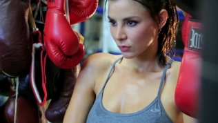 Close-up of Kacey Barnfield's face next to lots of boxing gloves